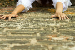 Girl in white dress climbs wall. Stock Photos