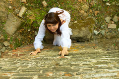 Girl in white dress climbs wall. Royalty Free Stock Photography