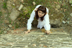 Girl in white dress climbs wall. Stock Photo