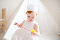 A girl in a white dress and crown plays Stock Photos