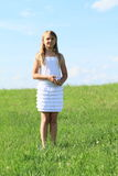 Girl in white dress. Cute little kid - blond girl in white dress standing on green grass of meadow Stock Image