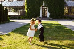 A girl in a white dress is dancing with a boy in a fashionable suit. royalty free stock image