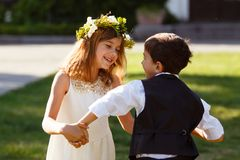 A girl in a white dress is dancing with a boy in a fashionable suit. royalty free stock photography