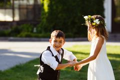 A girl in a white dress is dancing with a boy in a fashionable suit. stock image