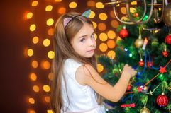A girl in a white dress decorates a festive Christmas tree stock photography