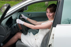 Girl in white dress driving a car Stock Photography