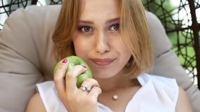 A girl in a white dress is eating a green apple. stock video
