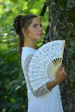 girl in white dress with fan Royalty Free Stock Photography