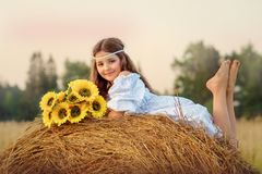 The girl in a white dress in the field lies in the summer on a haystack stock images