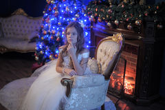 Girl in white dress in the fireplace Stock Images