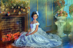 Girl in a white dress by the fireplace at christmas Royalty Free Stock Photo