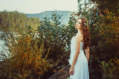 Girl in white dress in forest. Beautiful girl in the woods in a white dress with headscarf Royalty Free Stock Photography