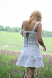Girl in white dress going away on meadow. Morning Stock Photos