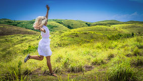 A girl in white dress happy jumping on green grass Hill, Teletubbies Hills, Nusa Penida, Bali, Indonesia Royalty Free Stock Image