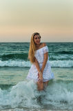 A girl in white dress having fun in the sea Stock Photography