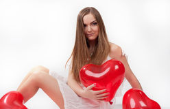 Girl in white dress with heart-shaped baloons Stock Photography