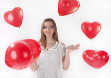 Girl in white dress with heart-shaped baloons Stock Images