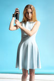 girl in a white dress holding a bottle with hairspray Stock Photo