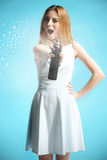 girl in a white dress holding a bottle with hairspray Royalty Free Stock Photos