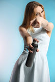 Girl in a white dress holding a bottle with hairspray Stock Photography