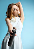 girl in a white dress holding a bottle with hairspray Royalty Free Stock Photography