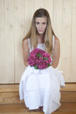 Girl in white dress holding bouquet Stock Photography