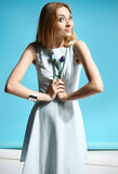 Girl in a white dress holding a flowers Stock Image