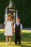A girl in a white dress holds a boy`s hand in a fashionable suit royalty free stock photos
