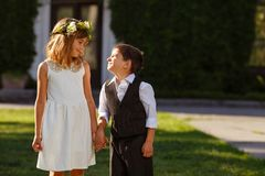A girl in a white dress holds a boy`s hand in a fashionable suit royalty free stock photo