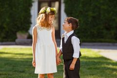 A girl in a white dress holds a boy`s hand in a fashionable suit royalty free stock photography