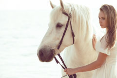 Girl in white dress with horse on the beach. Beautiful bride in white wedding dress with horse on the beach Stock Image