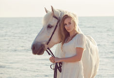 Girl in white dress with horse on the beach. Beautiful bride in white wedding dress with horse on the beach Stock Photos