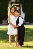 A girl in a white dress hugs a boy in a fashionable suit. stock images