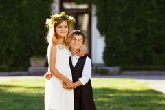 A girl in a white dress hugs a boy in a fashionable suit. royalty free stock images