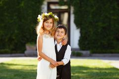 A girl in a white dress hugs a boy in a fashionable suit. royalty free stock image