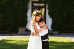 A girl in a white dress hugs a boy in a fashionable suit. stock photography