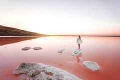 The girl in the white dress on the lake the color of living coral, royalty free stock images