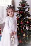 Girl in white dress with lantern under Christmas tree Stock Image