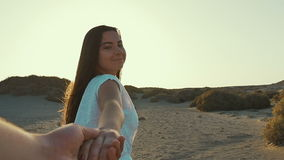 The girl in white dress leading a man forward to the adventure. Follow me concept. Slow motion. Sunset stock footage