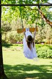 Girl in white dress swinging on the swings royalty free stock image