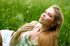 Girl in white dress lying in the grass Stock Images