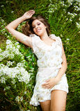 Girl in white dress lying on grass with white flowers Royalty Free Stock Images