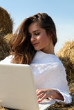 Girl in white dress lying on hay with laptop Royalty Free Stock Photos
