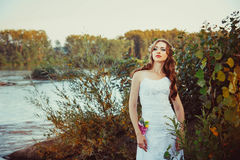 Girl in white dress near the river. Girl bride is in a dress by the river at sunset Stock Photo