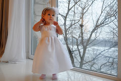 Girl in white dress next to a large window Royalty Free Stock Photo
