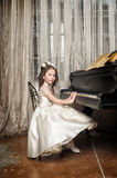 Girl in white dress at the piano. Girl at the piano in a retro interior Royalty Free Stock Photos