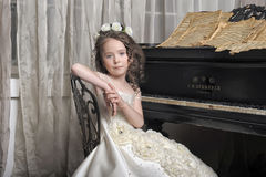 Girl in white dress at the piano Royalty Free Stock Photography