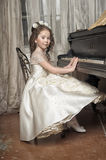Girl in white dress at the piano. Girl at the piano in a retro interior Royalty Free Stock Photography
