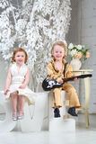 girl in white dress and pop musician with guitar sit Royalty Free Stock Photo