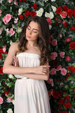 Girl in white dress posing on floral background Royalty Free Stock Images